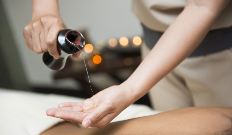 chiropractor pour oil into hand for massage, oil massage