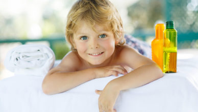 Adorable little blond kid relaxing in spa with having massage.
